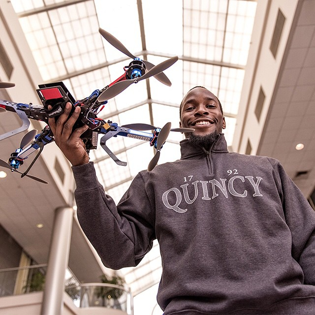 Student holding remote helicopter.