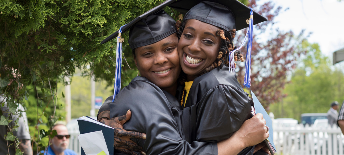 Two women hugging at graduation. more information about the quincy college trust opportunity scholarship